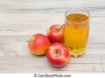 ripe red apples and glass of juice on a wooden table