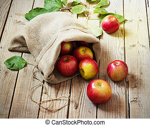Ripe red apples in a bag on wooden background