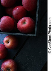 Ripe red apples in wooden box.