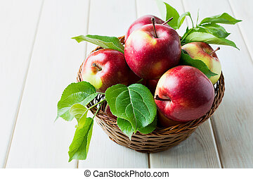 Ripe red apples with green leaves
