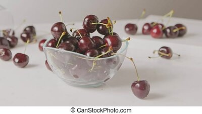 Ripe red cherries with droplets of water fall into a glass...