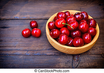 Ripe red cherry in a wooden plate, top view
