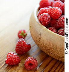 Red Juicy Raspberries in the Wooden Bowl on the Wooden Table
