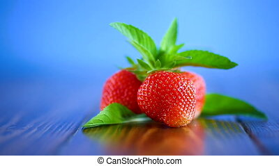ripe red organic strawberry on a blue background