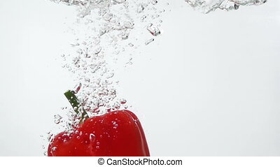 Ripe Red Pepper Falling Through Water.