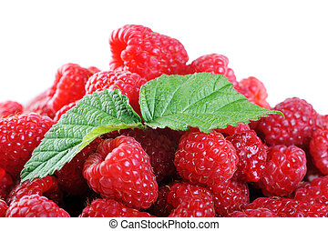 Ripe red raspberries with green leaves close up