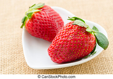 Ripe red strawberries in white cup.