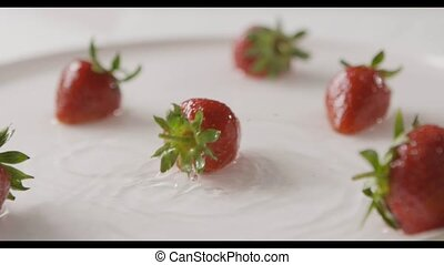 Ripe red strawberry fruit falls into the center of a plate of water with splashes and drops of water. A few berries lie on the white plate. Slow motion. Full HD video, 240fps,1080p.