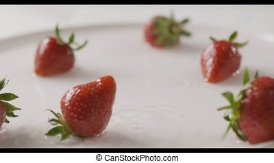 Ripe red strawberry fruit falls into the center of a plate of water with splashes and drops of water. A few berries lie on the white plate. Slow motion. Out of focus. Full HD video, 240fps,1080p.