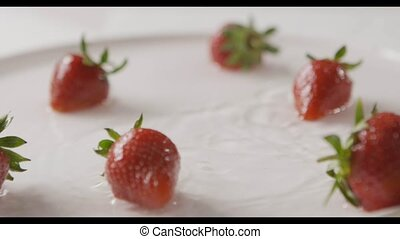 Ripe red strawberry fruit falls into the center of a plate...