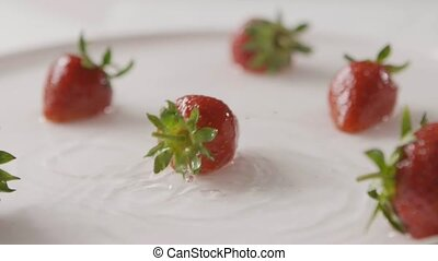 Ripe red strawberry fruit falls into the center of a plate ...