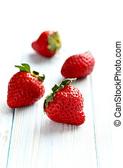 Ripe red strawberry on a blue wooden table