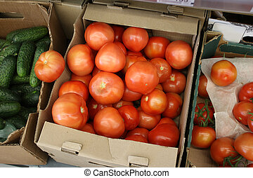 Ripe red Tomatoes in the store are in cardboard boxes, next to the green cucumbers.