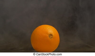 Ripe rotating orange fruit from which evaporation and...