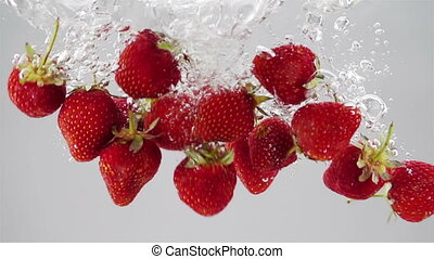 Ripe Strawberries Falling through the Water.