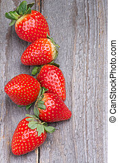 Ripe Strawberries Full Body In a Row isolated on Wooden background. Top View