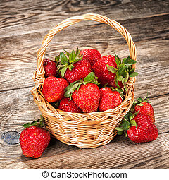 Ripe strawberries in a basket on an old table