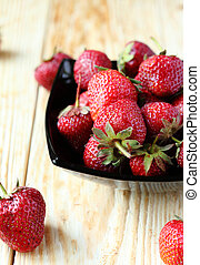 ripe strawberries in a bowl on the table