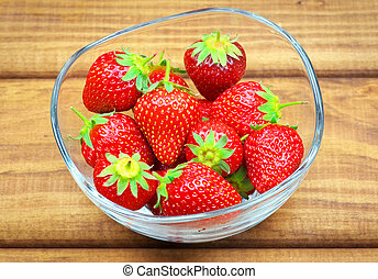 Ripe strawberries in a glass bowl on wooden table.