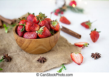 ripe strawberries in a wooden bowl on a white table