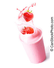 Ripe red fresh strawberries splashing into a glass of blended fruit smoothie with creamy yoghurt