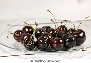 Ripe sweet cherries on a glass plate on a light wooden background