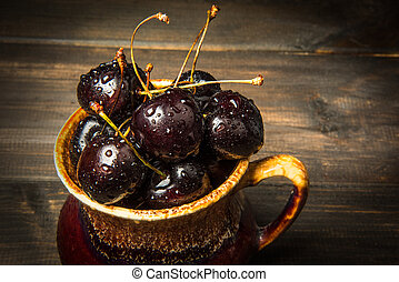 Ripe sweet cherry berries with drops in a brown earthenware plate on a wooden surface.