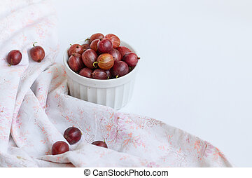 Ripe sweet gooseberry berries in a white bowl on a white table.