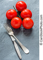 Ripe tomatoes and cutlery. - Red tomatoes on branch, fork ...