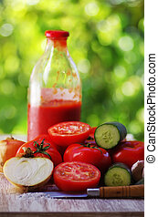 ripe tomatoes and glass bottle of tomato paste