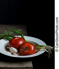 Ripe tomatoes and scallions on old wooden table.