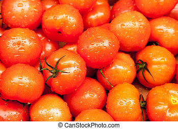 Ripe tomatoes at market wet with rain