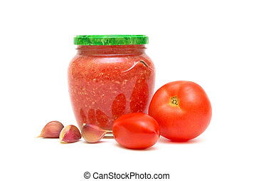Ripe tomatoes, garlic and Caucasian sauce adjika in a glass jar on a white background closeup