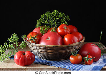 Ripe tomatoes in a basket on the table.