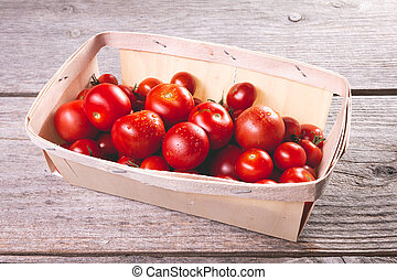 ripe tomatoes in a small wooden crate