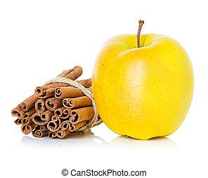 Ripe yellow apple with cinnamon sticks