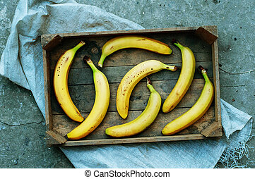 ripe yellow bananas in wicker basket, on wooden background, view from above, yellow fruits, yellow bananas in a wooden box, food, meal, vitamins