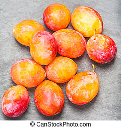 Ripe Yellow Plums on grey stone table top view. Fresh plumps with copy space