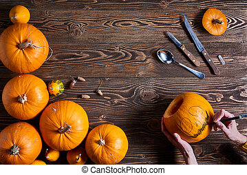 Ripe yellow pumpkins over wooden background - Hands carving...