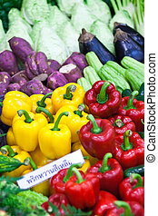 Ripe Yellow, Red and Green Peppers in Vegetables Market