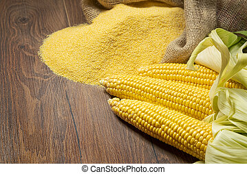 Ripe young sweet corn cob and cornmeal on brown background