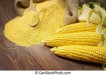Ripe young sweet corn cob spoon and cornmeal
