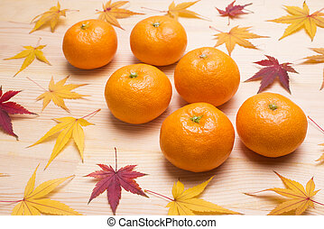 Ripening Mikan and autumn maple leaves on wood table