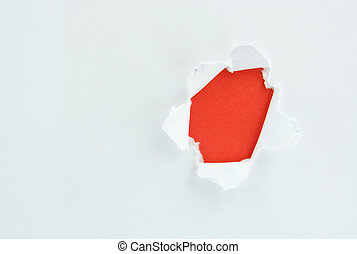 Ripped white paper against a red background