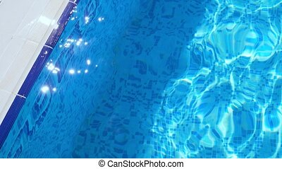 Ripple on blue water in the pool with light reflections.
