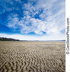 Rippled sand and mud beach created by low tide in White Rock near Vancouver, Canada. Beach background with copy space.