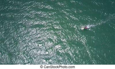 rippling ocean waves gleam under sunlight around surfer -...