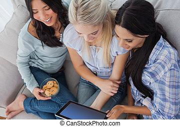 rir, amigos, usando, tablete digital, junto, e, comer, biscoitos, casa, ligado, sofá