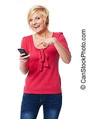 rir, mulher aponta, ligado, telefone móvel