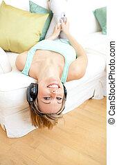 rir, mulher jovem, escutar, música, mentindo, ligado, um, sofá
